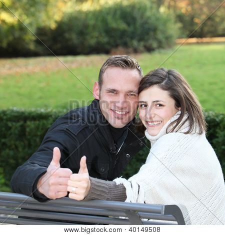 Happy Young Couple Giving A Thumbs Up