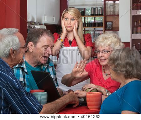 Young Waitress And Arguing Seniors