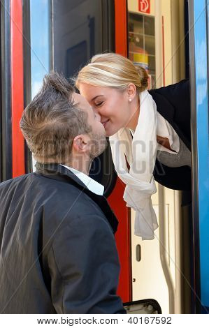 Man kissing woman goodbye train leaving romance couple commuter journey
