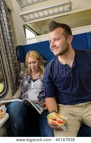 Man looking out train window woman magazine sandwich reading smiling