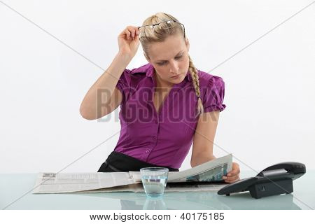 Blond office worker reading newspaper