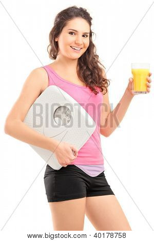 A smiling female athlete holding a weight scale and glass of orange juice isolated on white background