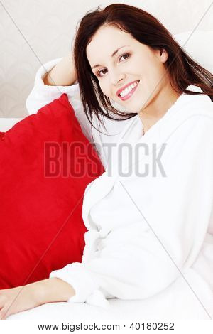 Portreit of a young smiling woman sitting on a couch with a red pillow, dressed in dressing-gown.