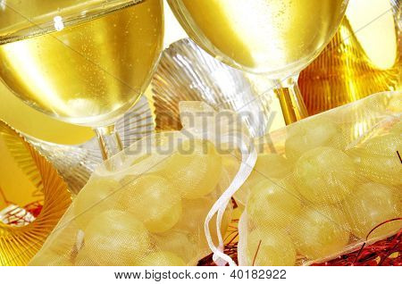 some glasses with spanish cava and sachets with the twelve grapes of luck, traditional on the New Year