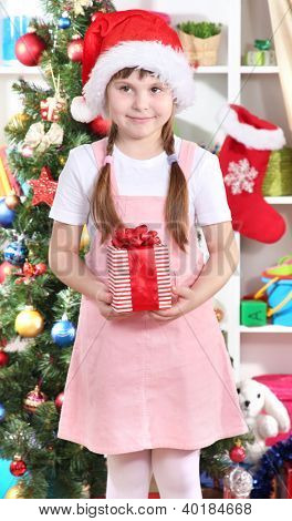 Happy little girl with Christmas toys in festively decorated room