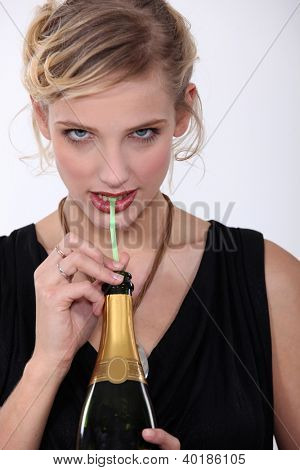 Woman drinking champagne through a straw