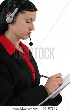 Woman with headset writing on notepad