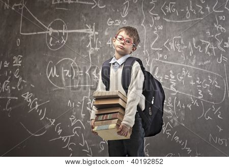 Child with backpack holding some school books with a blackboard in the background
