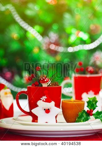Picture of luxury Christmastime table setting, beautiful still life of utensil on decorated Christmas tree background, red tea cup with candle and Santa Claus star on festive white plate