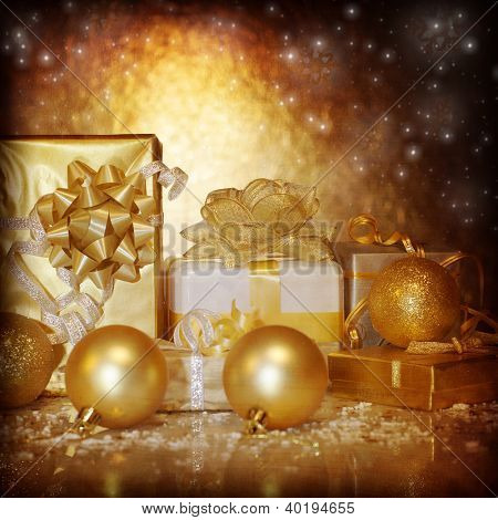 Image of traditional New Year gifts, Christmas present box wrapping in shiny golden festive paper, Christmastime still life isolated on dark glowing background, Xmas eve, holiday surprise