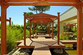 pic of pergola  - Landscape with wood pavilion deck and tropical plants in summer resort - JPG