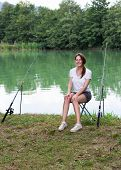 stock photo of fisherwomen  - Brunette Woman Fishing at a lake with green water - JPG