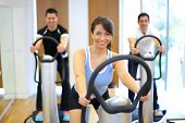 foto of vibration plate  - Group of two men and one woman on a vibration massage plate in a gym