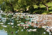 stock photo of plastic bottle  - heavy plastic pollution in wild beautiful landscape