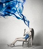 picture of exhale  - Beautiful woman exhales a blue smoke - JPG