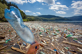 image of water pollution  - hand throwing plastic bottle in beautiful landscape ruined by pollution bicaz lake romania - JPG