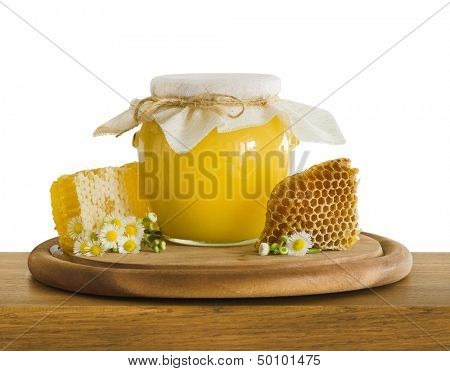 glass jar of honey and honeycombs on wooden table