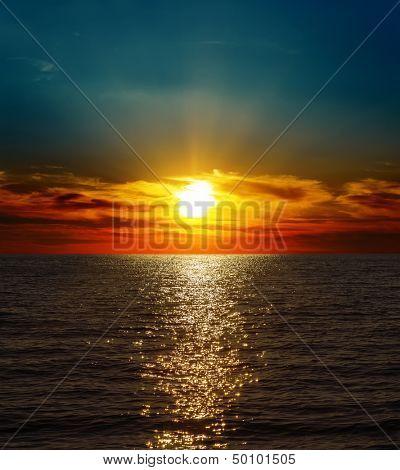 dramatic sunset over dark water