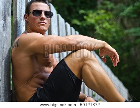 Handsome, Serious Muscleman Sitting Against Wood Fence