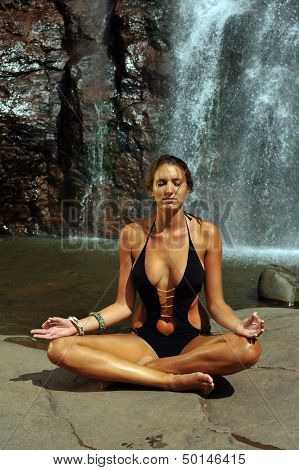 Beautiful girl wearing black one piece swimsuit meditating in lotus yoga pose
