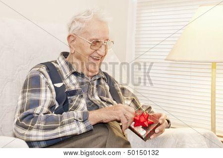 Elderly Man Opening Gift