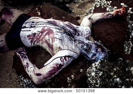 young man with a zombie body painting, covered with blood on the beach  (halloween topic)