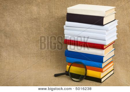Big Pile Of Books And Magnifier Glass