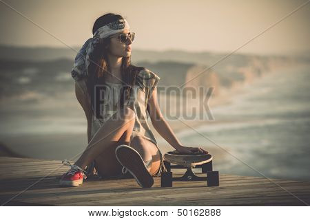 Beautiful young woman sitting over a skateboard