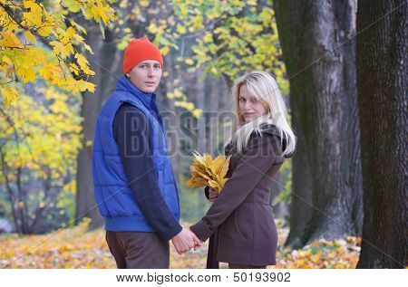 Lovers male and female walking in the autumn park