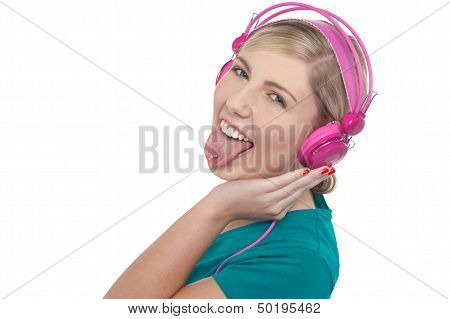 Woman With Headphones On Sticking Her Pierced Tongue Out