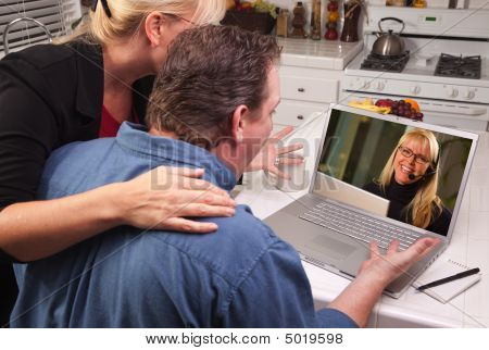 Casal na cozinha usando o Laptop - suporte ao cliente