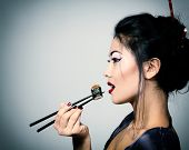 foto of chopsticks  - Young beautiful asian woman eating sushi with chopsticks - JPG