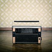 stock photo of transistor  - vintage radio receiver device on the weathered wooden parquet floor in vintage room with old fashioned wallpaper - JPG
