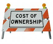image of barricade  - The words Cost of Ownership on a barricade to illustrate the prohibitive true price of a car - JPG
