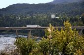 stock photo of semi trailer  - A semi truck driving over a highway bridge near Castlegar - JPG