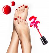 stock photo of nail-design  - Beautiful female legs with red pedicure and nail polish bottle with brush - JPG