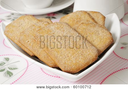 a pile of cinnamon cookies in a plate in a set table