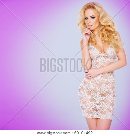 Glamorous young blond woman with a shapely figure in a sexy see-through lacy white dress against a violet background