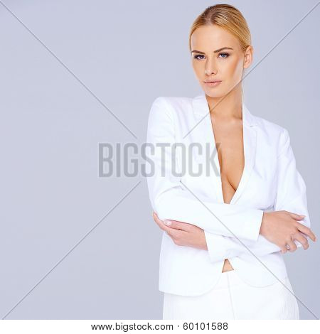 Elegant blond woman wearing a white suit with a plunging neckline giving a view of her breast standing sideways looking thoughtfully at the camera with copyspace