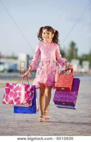 Cute Girl Holding Shopping Bags And Walking In The Street