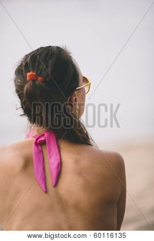 model sitting on a sandy beach