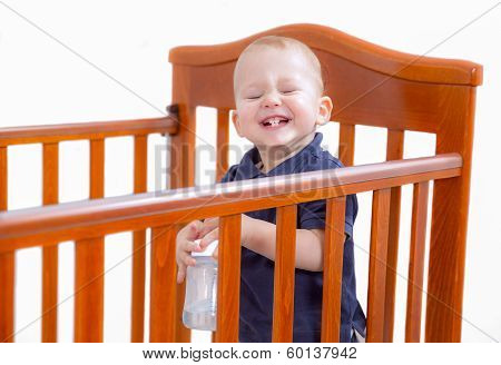 Baby boy standing and laughing in crib