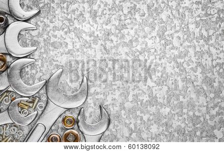 Wrench tools and nuts on a light textured metallic background with space for text