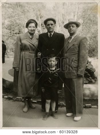 KIEV, UKRAINE, USSR - CIRCA 1950s: An antique photo shows outdoor portrait of a Soviet family - father, mother, son and grandfather