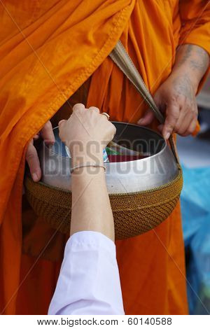 Hand Put Food Offerings In A Buddhist Monk's Alms Bowl