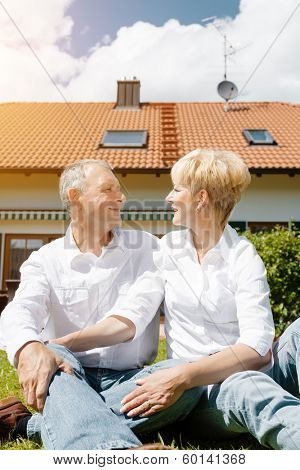 Senior couple of man and woman sitting in garden in front of home