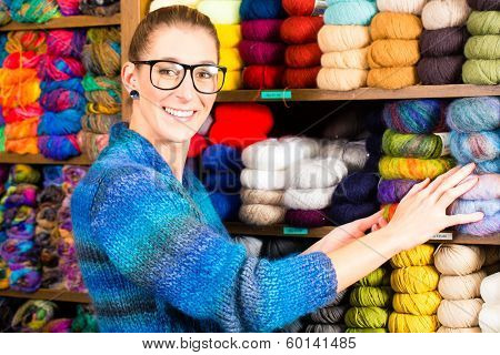 Young woman buying colorful wool and yarn for their hobby in a knitting shop