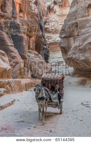 PETRA, JORDAN - MAY 11, 2013: people in horse cart at the Siq path in Nabatean