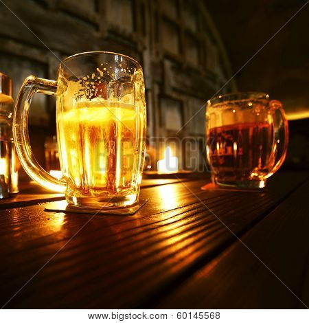 Mugs of beer in dark bar close-up