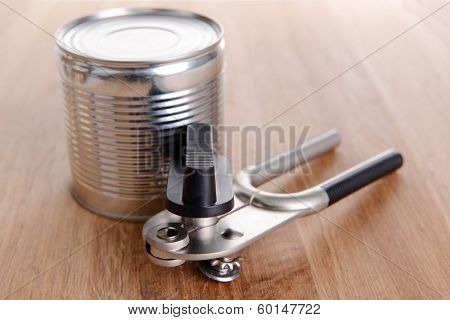 Can piercer with canned on wooden background